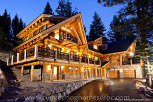 Pioneer Log Homes at night with golden night lights